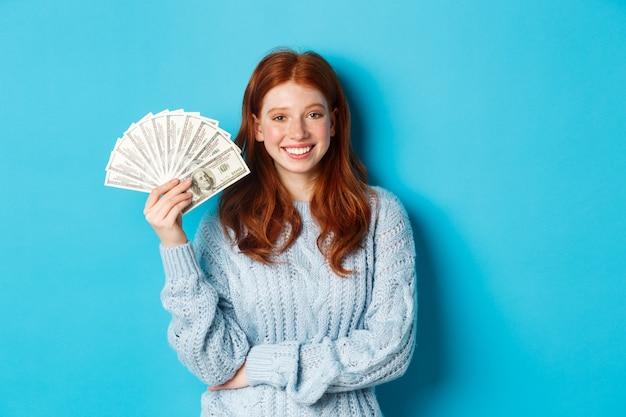 お金を持って笑顔で、自信を持って気楽に見え、青い背景にセーターを着て立っている、幸せで気ままな赤毛の女性。