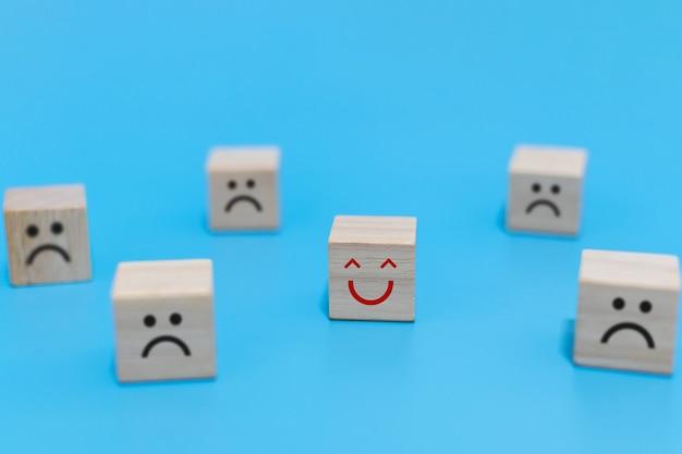 幸せと不幸な感情。青い背景、前向きな考え、社会問題、顧客満足、前向きな態度、楽観主義と悲観主義の概念の木製の立方体に悲しい顔と幸せな笑顔