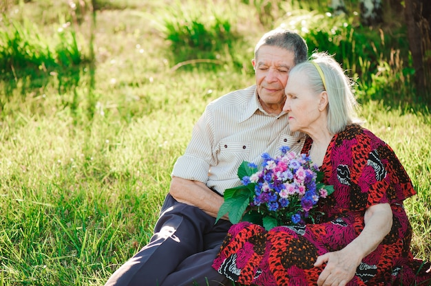 公園に座っている幸せで非常に年配の人々。