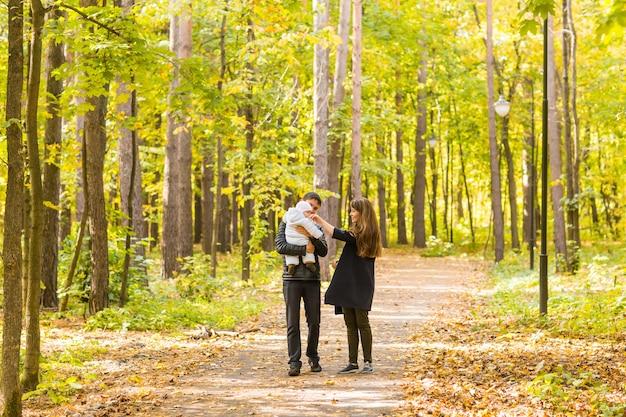 황금과 화려한 autum 자연에서 함께 휴식 행복하고 젊은 가족.