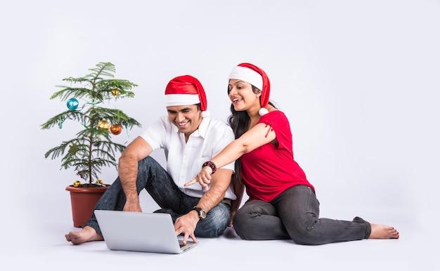 クリスマスを祝っている間ラップトップを使用してソファで幸せで若いインドのカップル