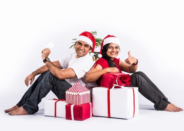 白い背景の上に、クリスマスプレゼントと幸せで若いインドのカップル