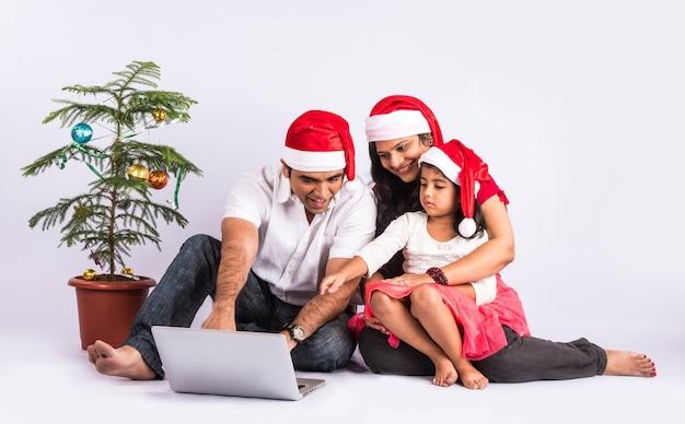 Счастливая и молодая индийская пара с девушкой или дочерью с помощью ноутбука во время празднования рождества