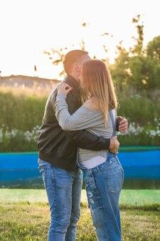 自然の中で抱き締める幸せで若い妊娠中のカップル
