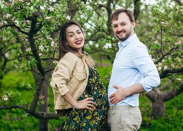 Счастливая и молодая беременная пара, обнимающаяся на природе