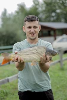 幸せな釣り人は、トロフィーの鯉を保持しています。鯉魚を持つ男。野外活動、釣り、魚を捕るコンセプト。