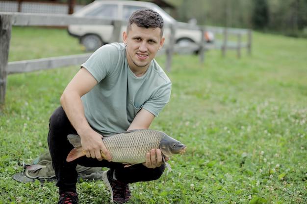 幸せな釣り人は、トロフィーの鯉を保持しています。鯉魚を持つ男。野外活動、釣り、魚を捕るコンセプト。 Premium写真
