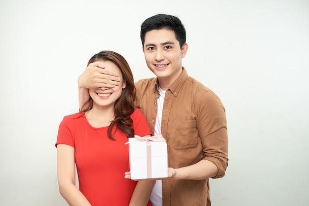 С юбилеем, дорогая! привлекательный азиатский мужчина закрывает глаза женщины, держа подарок для нее, белый фон