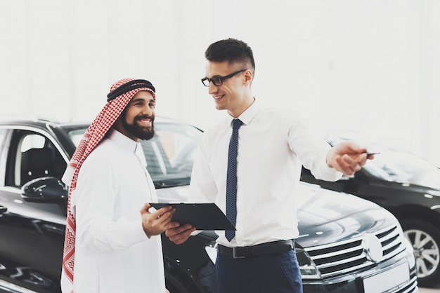Happy arab in car showroom agent holds papers.