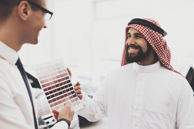Happy arab chooses car wood color with palette.