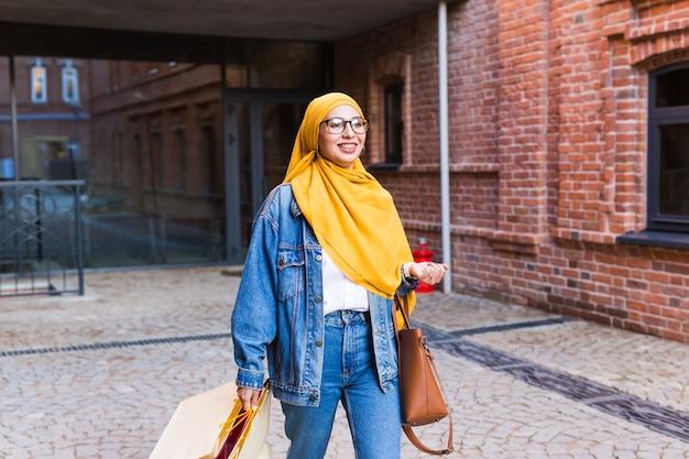 ショッピングバッグと幸せなアラブのイスラム教徒の少女