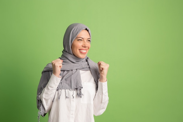 Happy arab woman in hijab. portrait of smiling girl, posing at green studio.