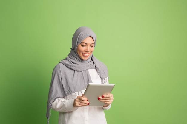 Happy arab woman in hijab with laptop. portrait of smiling girl, posing at green studio.