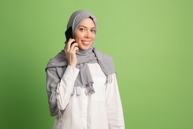 Happy arab woman in hijab with mobile phone. portrait of smiling girl, posing at green studio.