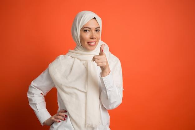 ヒジャーブの幸せなアラブの女性。赤いスタジオの背景にカメラを指して、笑顔の女の子の肖像画。若い感情的な女性。人間の感情、表情の概念。