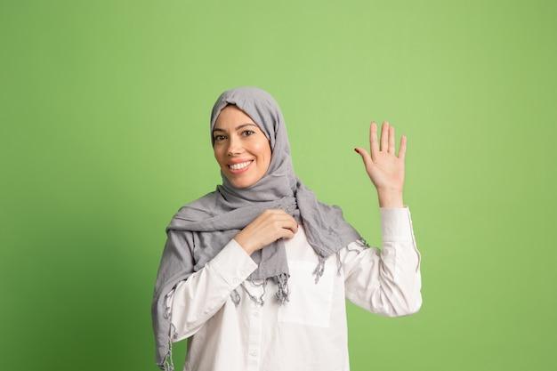 ヒジャーブの幸せなアラブの女性。緑のスタジオの背景でポーズをとって、笑顔の女の子の肖像画。