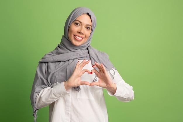 ヒジャーブの幸せなアラブの女性。緑のスタジオでポーズをとって、笑顔の女の子の肖像画。