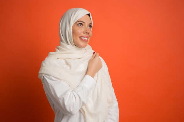 ヒジャーブの幸せなアラブの女性。赤いスタジオの背景でポーズをとって、笑顔の女の子の肖像画。若い感情的な女性。人間の感情、表情の概念。