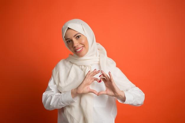 ヒジャーブの幸せなアラブの女性。赤いスタジオの背景でポーズをとって、笑顔の女の子の肖像画。若い感情的な女性。人間の感情、表情のコンセプト。正面図。