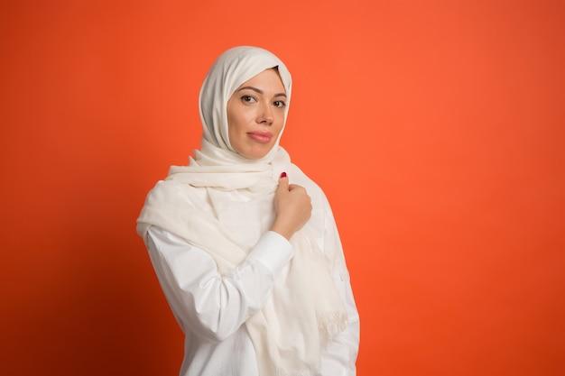 ヒジャーブの幸せなアラブの女性。赤いスタジオの背景でポーズをとって、笑顔の女の子の肖像画。