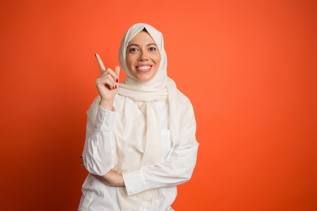 Hijab에서 행복 한 아랍 여자입니다. 빨간 스튜디오 배경에서 포즈 웃는 소녀의 초상화.