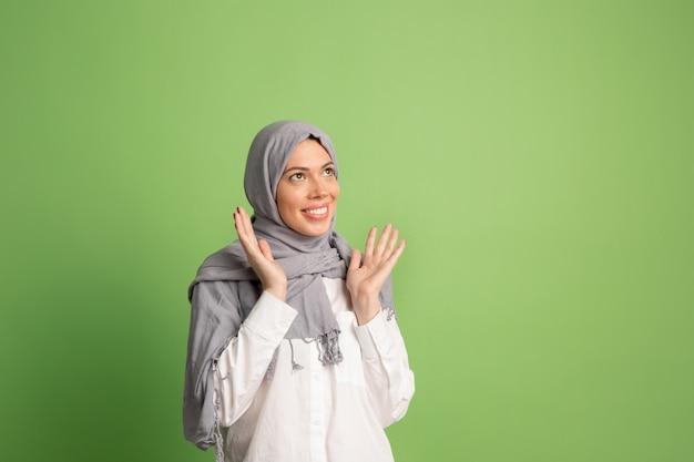 ヒジャーブで幸せなアラブの女性。スタジオの背景でポーズをとって、笑顔の女の子の肖像画