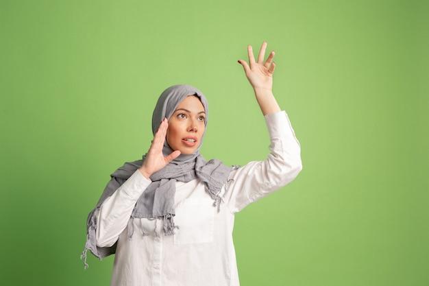 ヒジャーブの幸せなアラブの女性。緑のスタジオの背景で叫んで、笑顔の女の子の肖像画。若い感情的な女性。人間の感情、表情の概念。正面図。