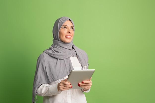 ラップトップとヒジャーブで幸せなアラブの女性。緑のスタジオの背景でポーズをとって、笑顔の女の子の肖像画。若い感情的な女性。人間の感情、表情の概念。正面図。