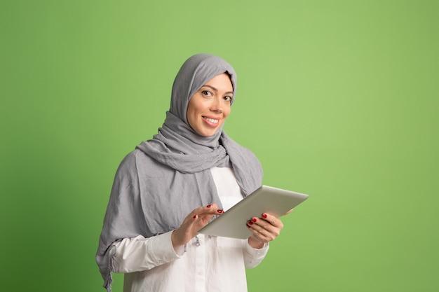 ラップトップとヒジャーブで幸せなアラブの女性。緑のスタジオの背景でポーズをとって、笑顔の女の子の肖像画。若い感情的な女性。人間の感情、表情のコンセプト。正面図。