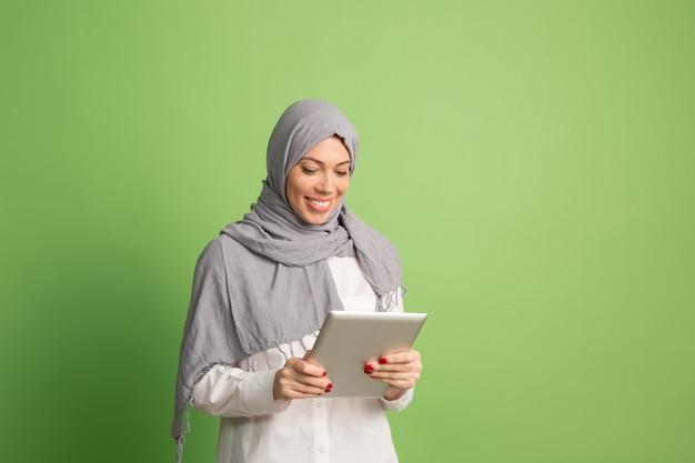 ラップトップとヒジャーブで幸せなアラブの女性。緑のスタジオでポーズをとって、笑顔の女の子の肖像画。