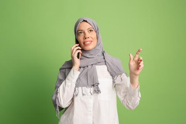 携帯電話でヒジャーブの幸せなアラブの女性。緑のスタジオの背景でポーズをとって、笑顔の女の子の肖像画。若い感情的な女性。人間の感情、表情の概念。正面図。
