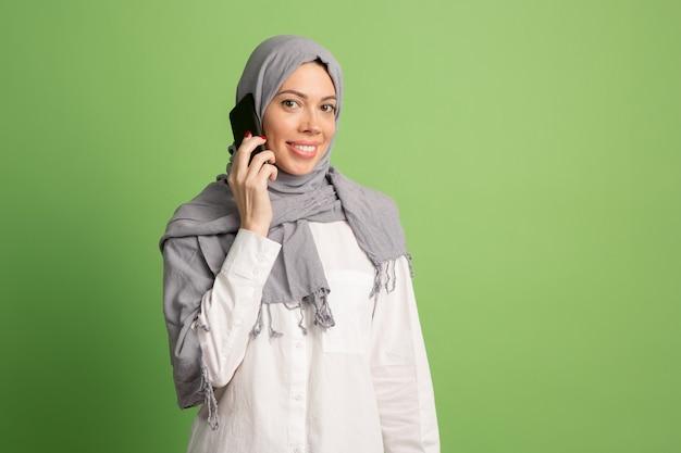 携帯電話でヒジャーブの幸せなアラブの女性。緑のスタジオでポーズをとって、笑顔の女の子の肖像画。