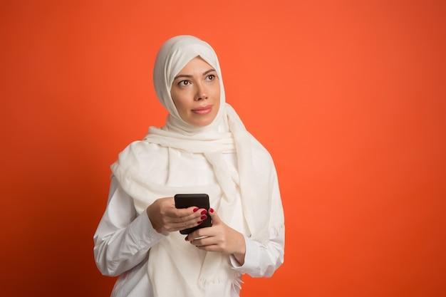 携帯電話でヒジャーブの幸せなアラブの女性。赤いスタジオの背景でポーズをとって、笑顔の女の子の肖像画。若い感情的な女性。人間の感情、表情のコンセプト。正面図。
