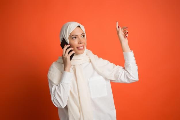 携帯電話でヒジャーブの幸せなアラブの女性。赤いスタジオの背景でポーズをとって、笑顔の女の子の肖像画。