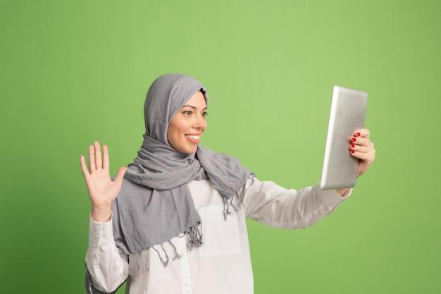 タブレットとヒジャーブで幸せなアラブの女性。緑のスタジオの背景でポーズをとって、笑顔の女の子の肖像画。