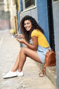 Happy arab woman sitting on urban step with a digital tablet