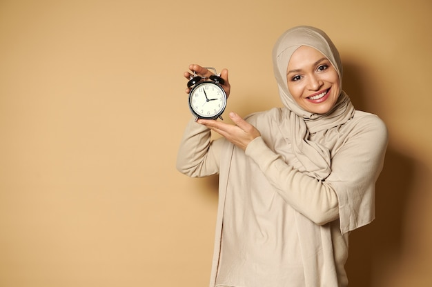 目覚まし時計を手に持って、コピースペースでベージュの表面に立っている間、正面に歯を見せる笑顔でかわいい笑顔のヒジャーブで覆われた頭を持つ幸せなアラブの女性