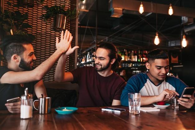 Счастливый арабский молодой человек дает пять своему другу