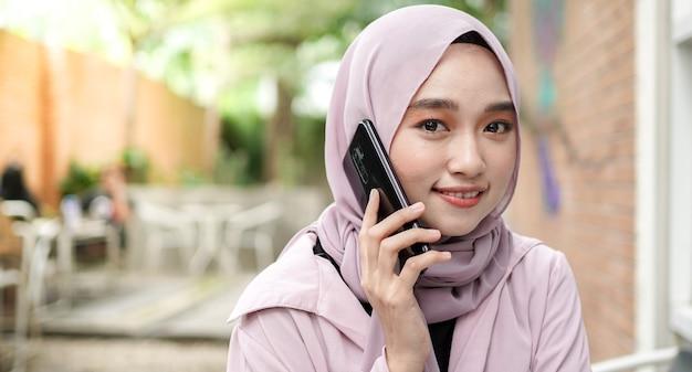 행복 한 아시아 히잡 여자 스마트 전화를 사용 하 고 전화, 카페에 앉아 커피를 마시는 프리미엄 사진
