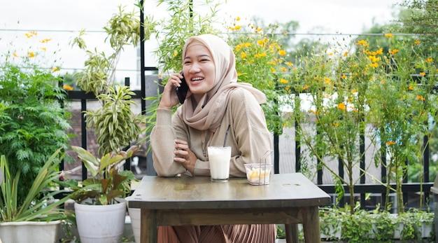 행복 한 아시아 Hijab 여자 스마트 전화를 사용 하 고 전화, 카페에 앉아 프리미엄 사진