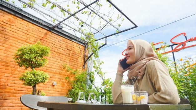 행복 한 아시아 hijab 여자 스마트 전화를 사용 하 고 전화, 카페에 앉아