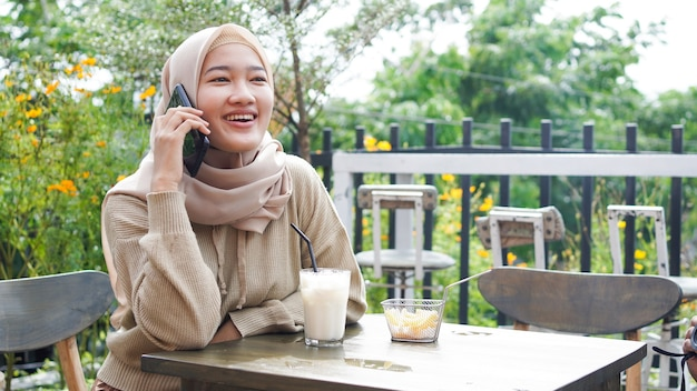 Happy asia hijab woman using smart phone and calling, sitting at cafe