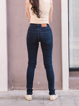 Happy asia woman in denim skinny jeans, midnight blue jeans, back view