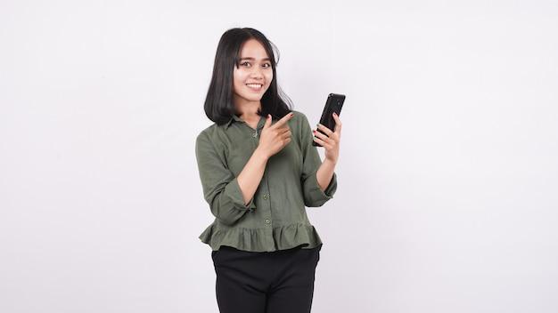 白い孤立した壁に電話を指している幸せなアジアの女性