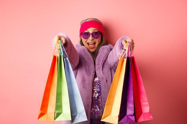 買い物に行く幸せなアジアの大人の女性、ショップバッグと手を伸ばして、ピンクの背景の上に立って、陽気な笑顔