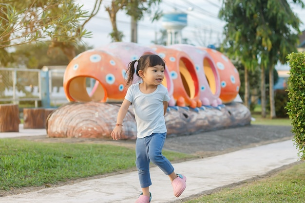 Happy asian baby girl running or jumping and playing at the park or garden field. she smiling and laughing.
