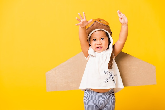 Happy asian beautiful funny baby little girl smile wear pilot hat raise hand up play and goggles with toy cardboard