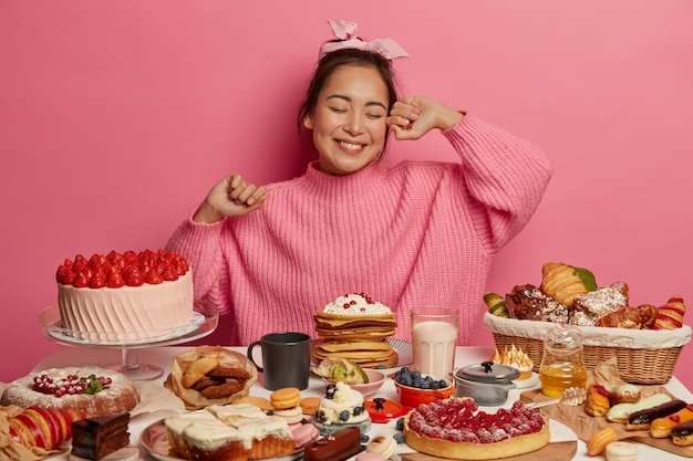 Happy asian birthday girl comes on tea party, eats sweet delicious cakes, surrounded by many desserts, poses against pink background.