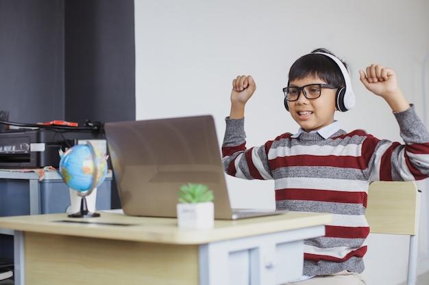 幸せなアジアの少年はラップトップから驚きを得る