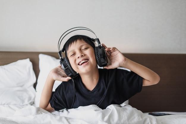 ベッドで音楽を聴いてヘッドフォンで幸せなアジアの少年